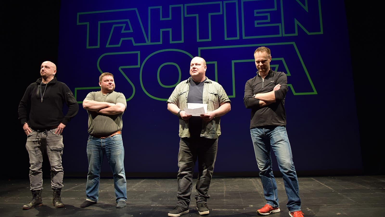 Neljä miestä seisoo näyttämöllä kertomassa Tahtien Sota -musiikkikomediasta