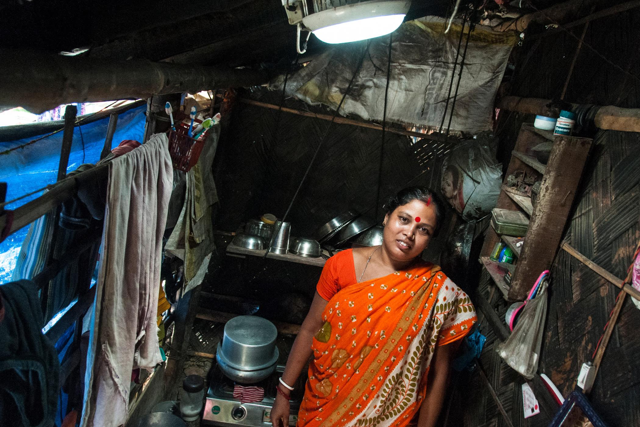 Nainen seisoo aurinkokupulampun alla keittiössä