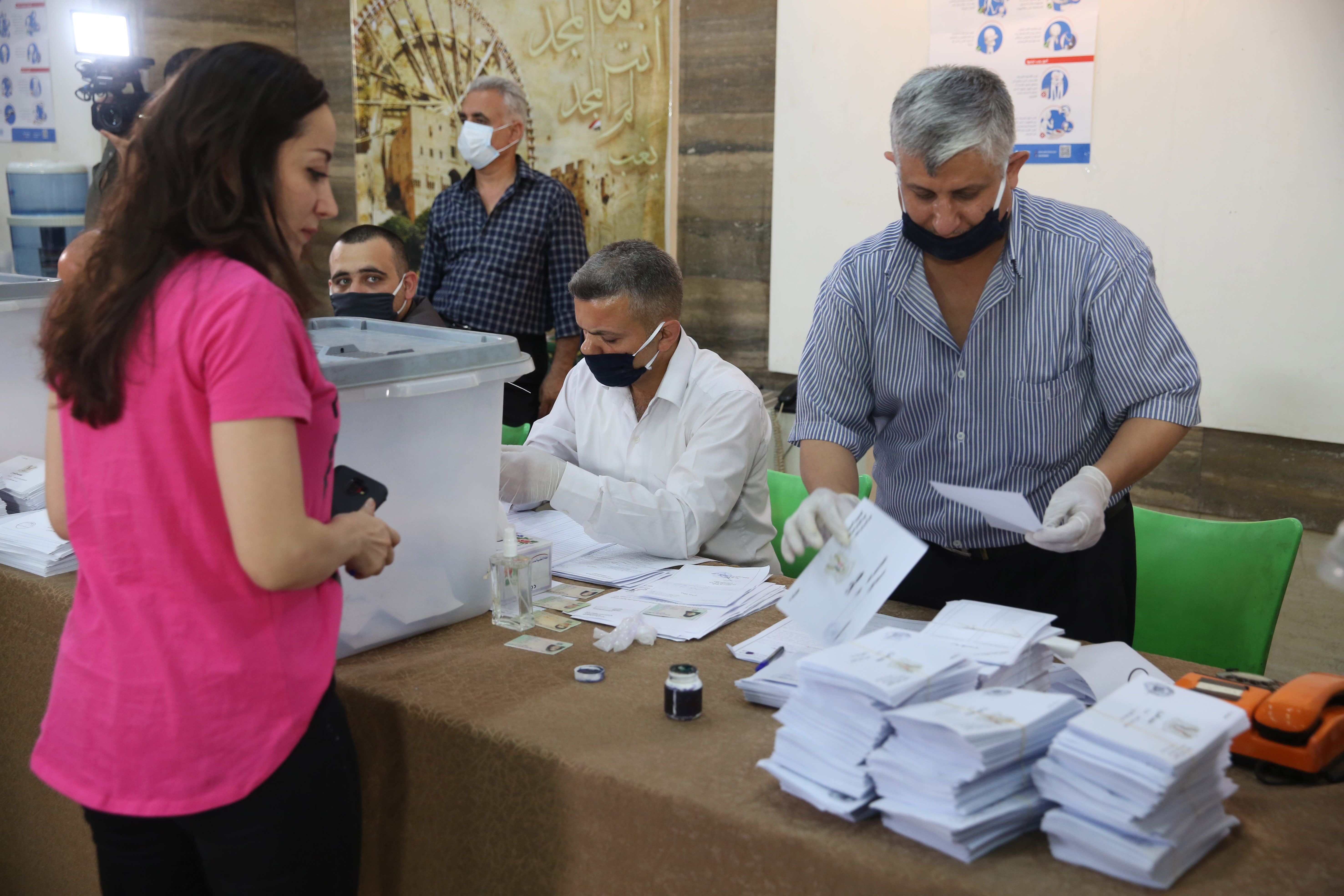 Nainen seisoo pöydän edessä, toisella puolella kasvomaskilla suojautunut vaalivirkailija nostelee äänestyslipukkeita