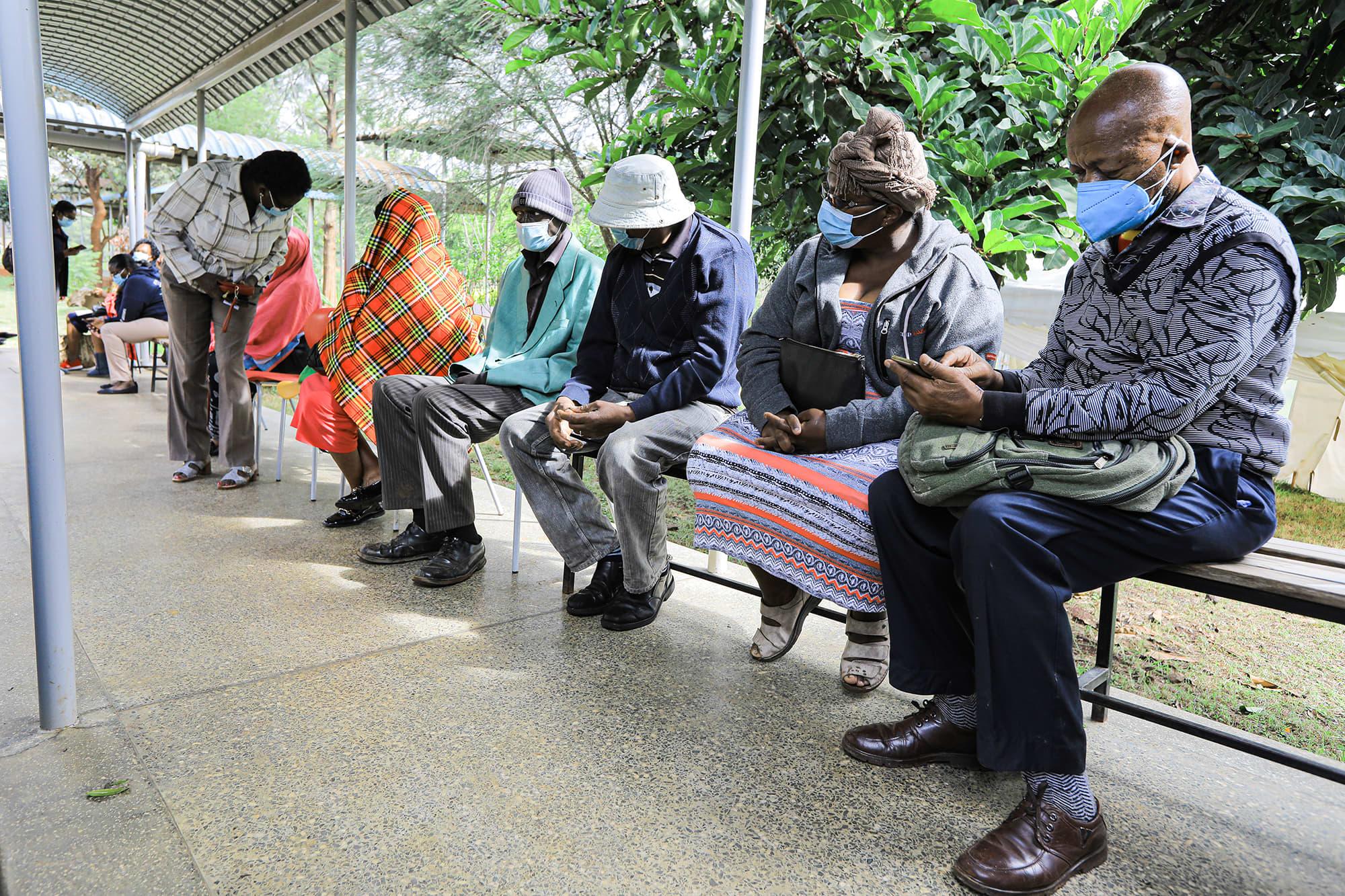 Ryhmä kenialaisia istuu ulkona odottamassa koronarokotetta.