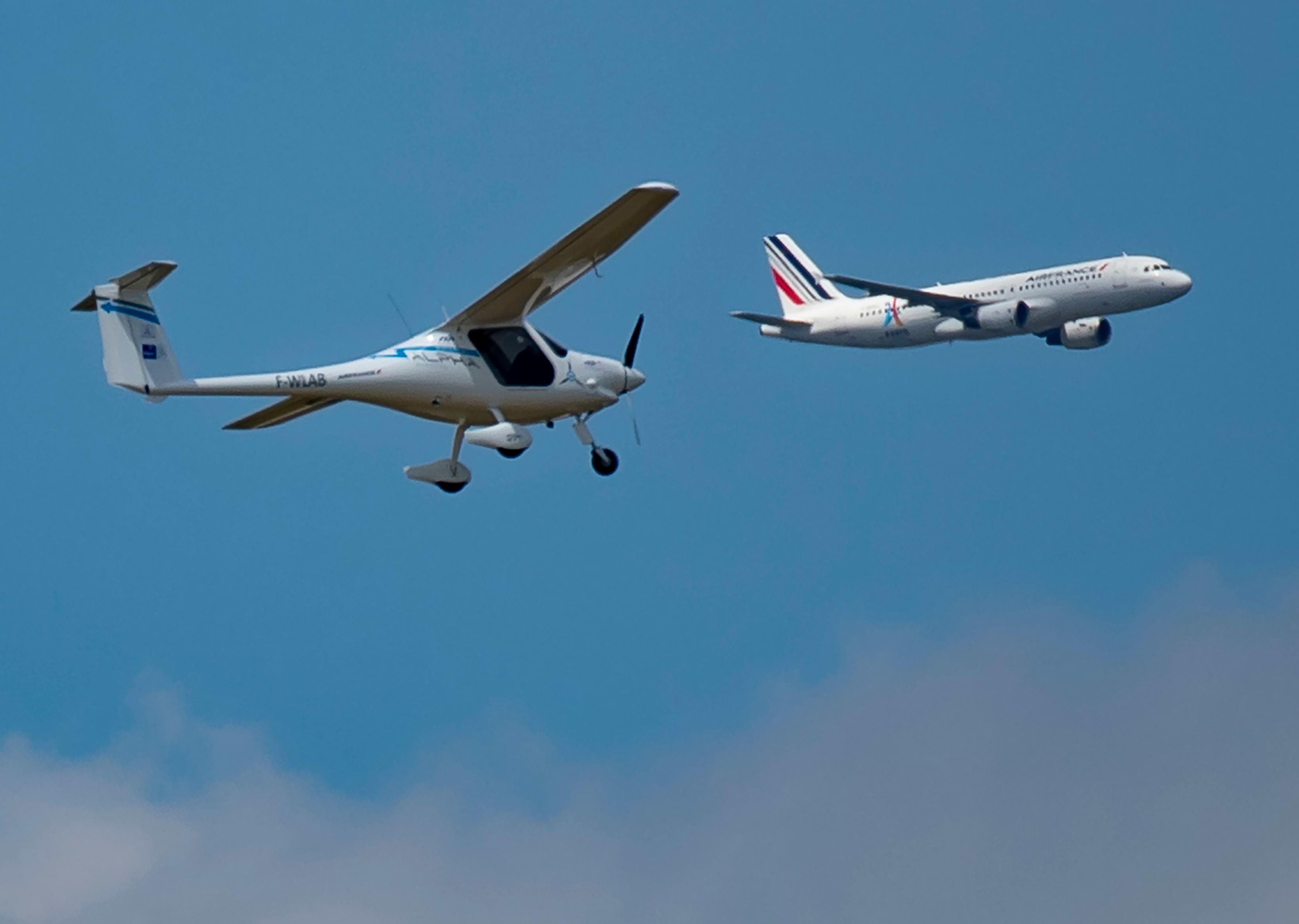 Pieni heiveröinen sähkölentokone lentää etualalla. Taustalla Air Francen Airbus.