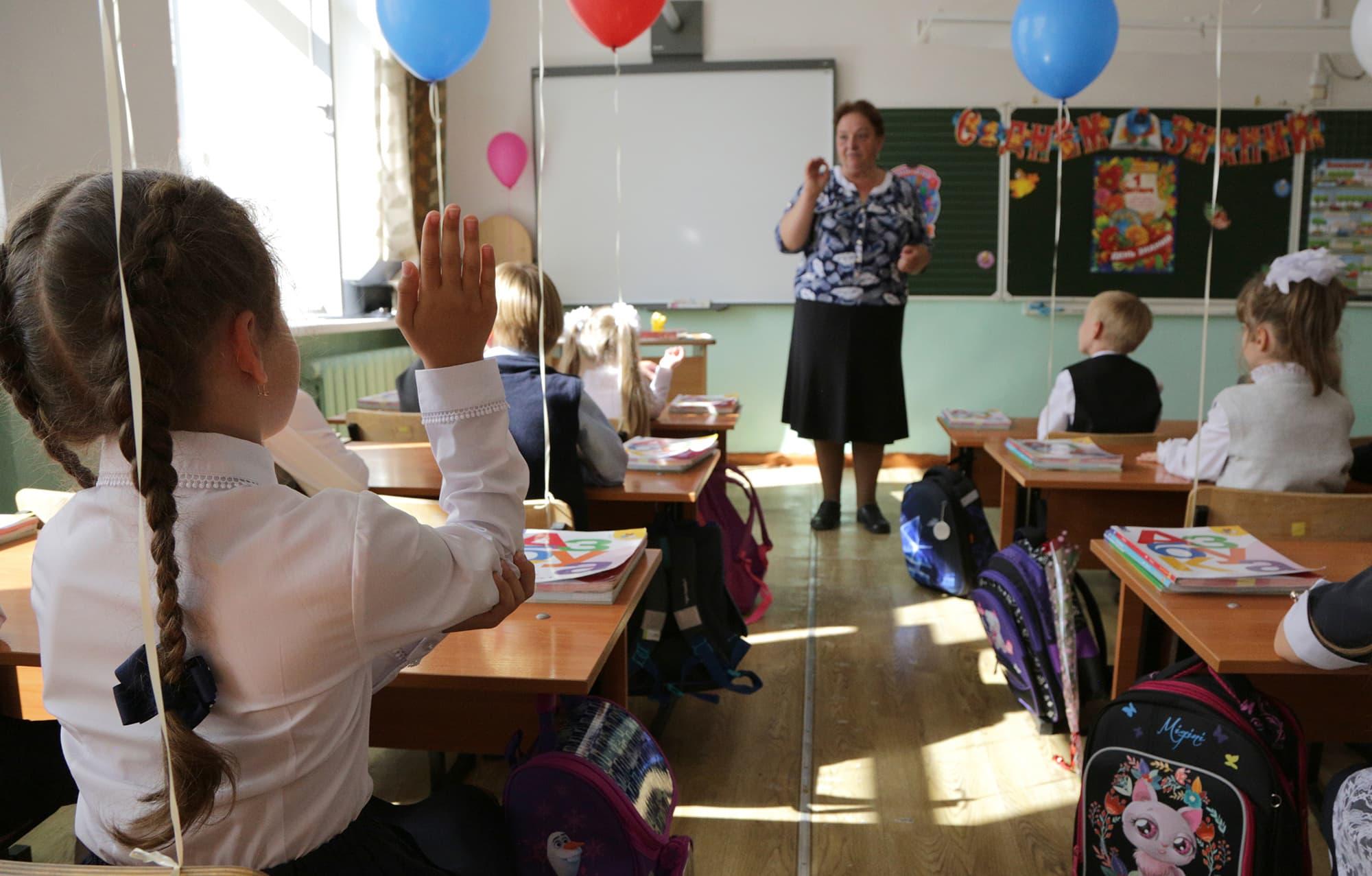 Ensimmäisen luokan oppilas viittoo venäläisessä luokkahuoneessa.