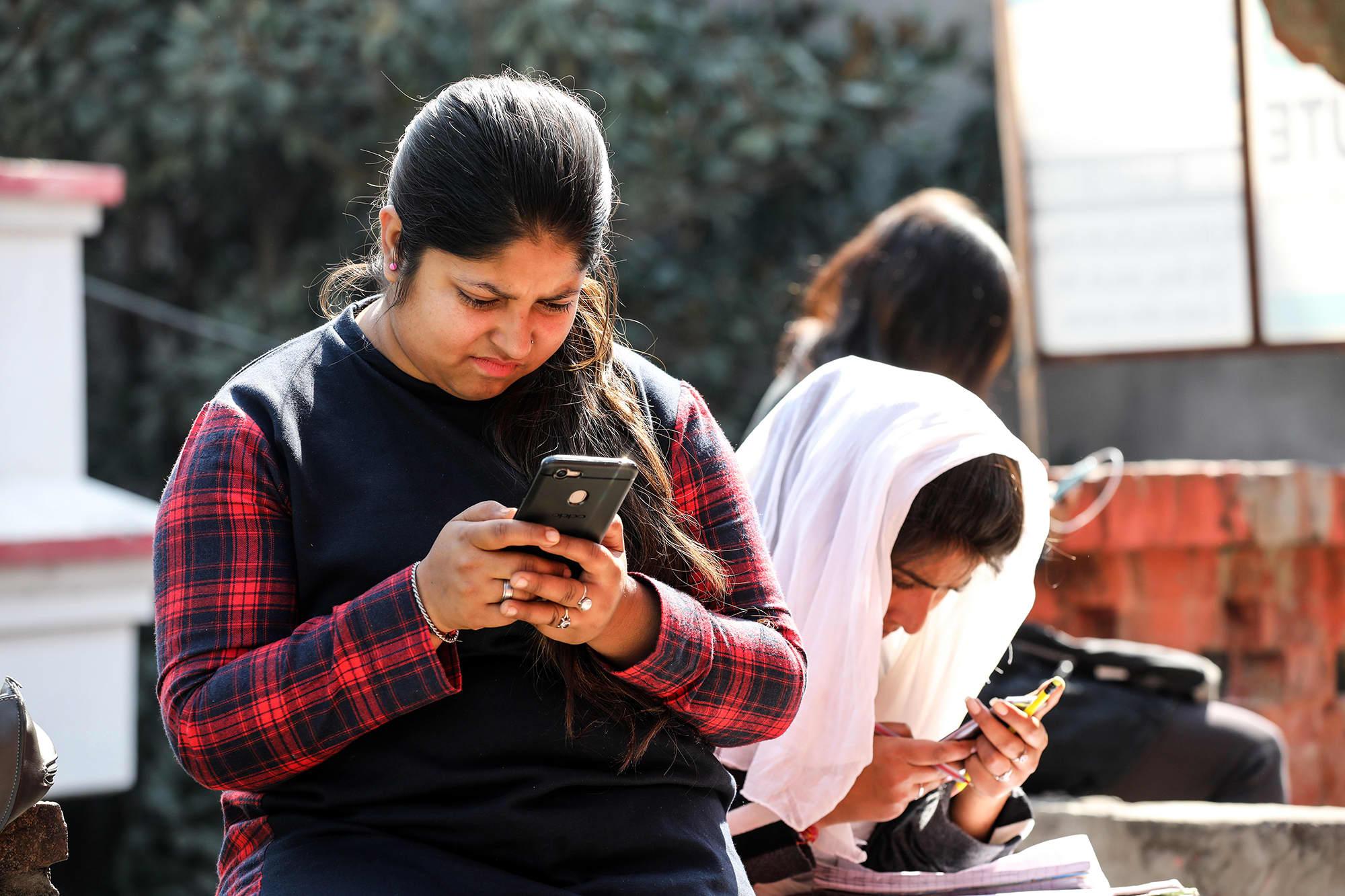 Intialaiset opiskelijat älypuhelimien kanssa internetissä.