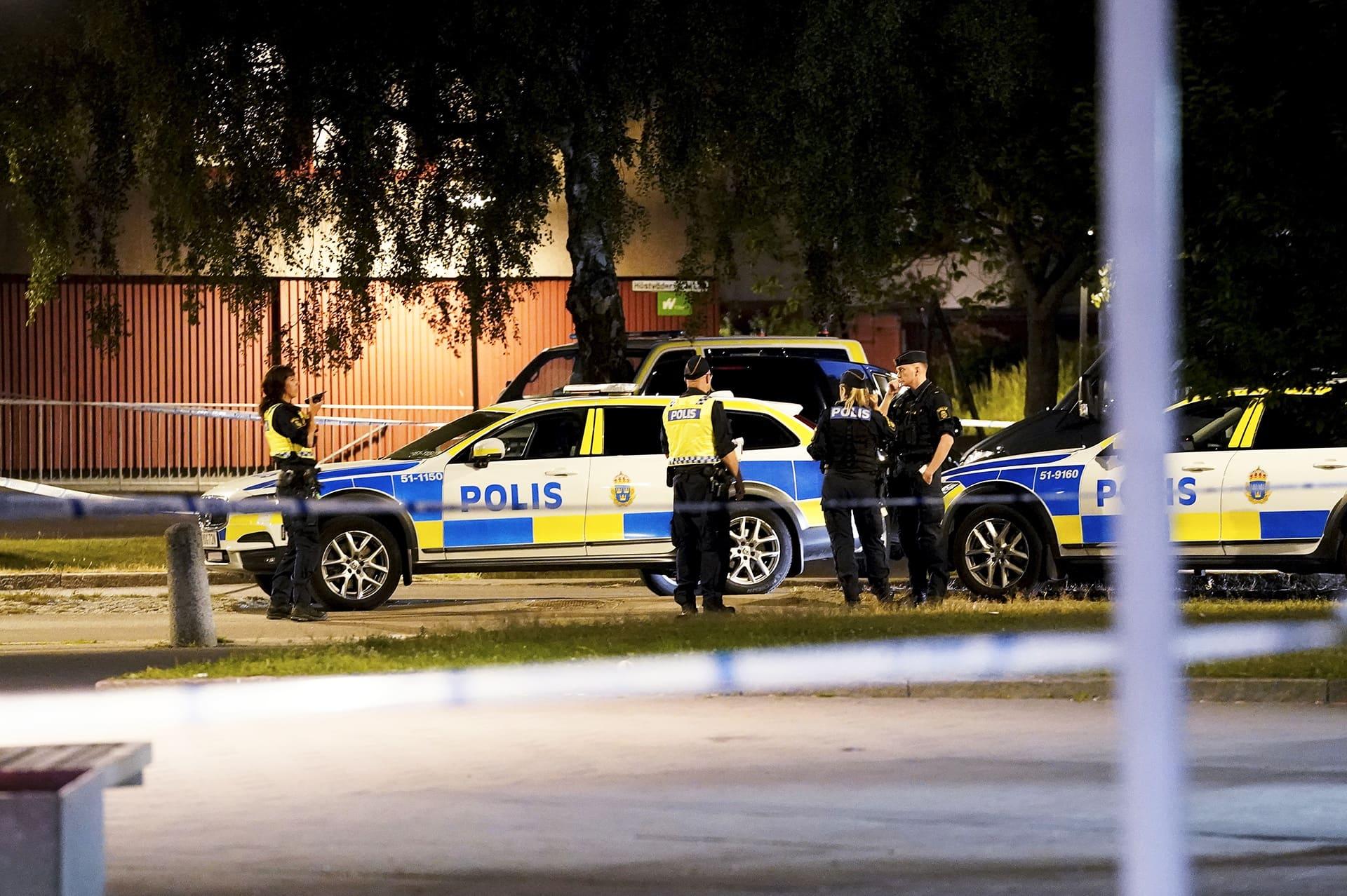 Poliiseja ja poliisiautoja ampumapaikalla.