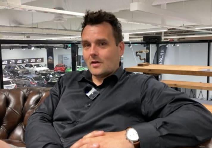 Autokauppias Joni Nelimarkka istuu työpaikallaan tuolissa toimittajan haastateltavana.