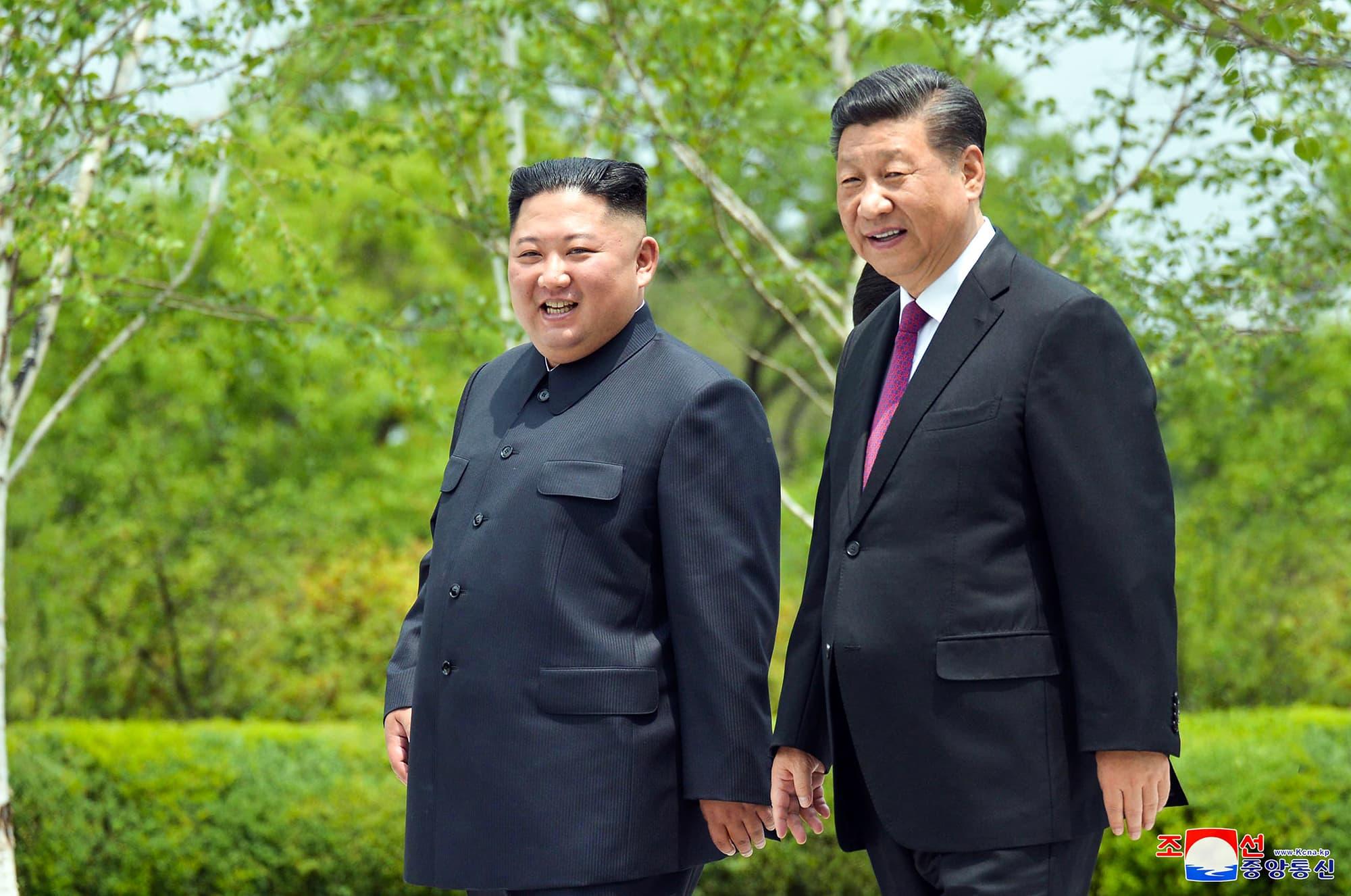 Kim Jong-un ja Xi Jinping kävelevät vihreässä puistomaisessa maisemassa.