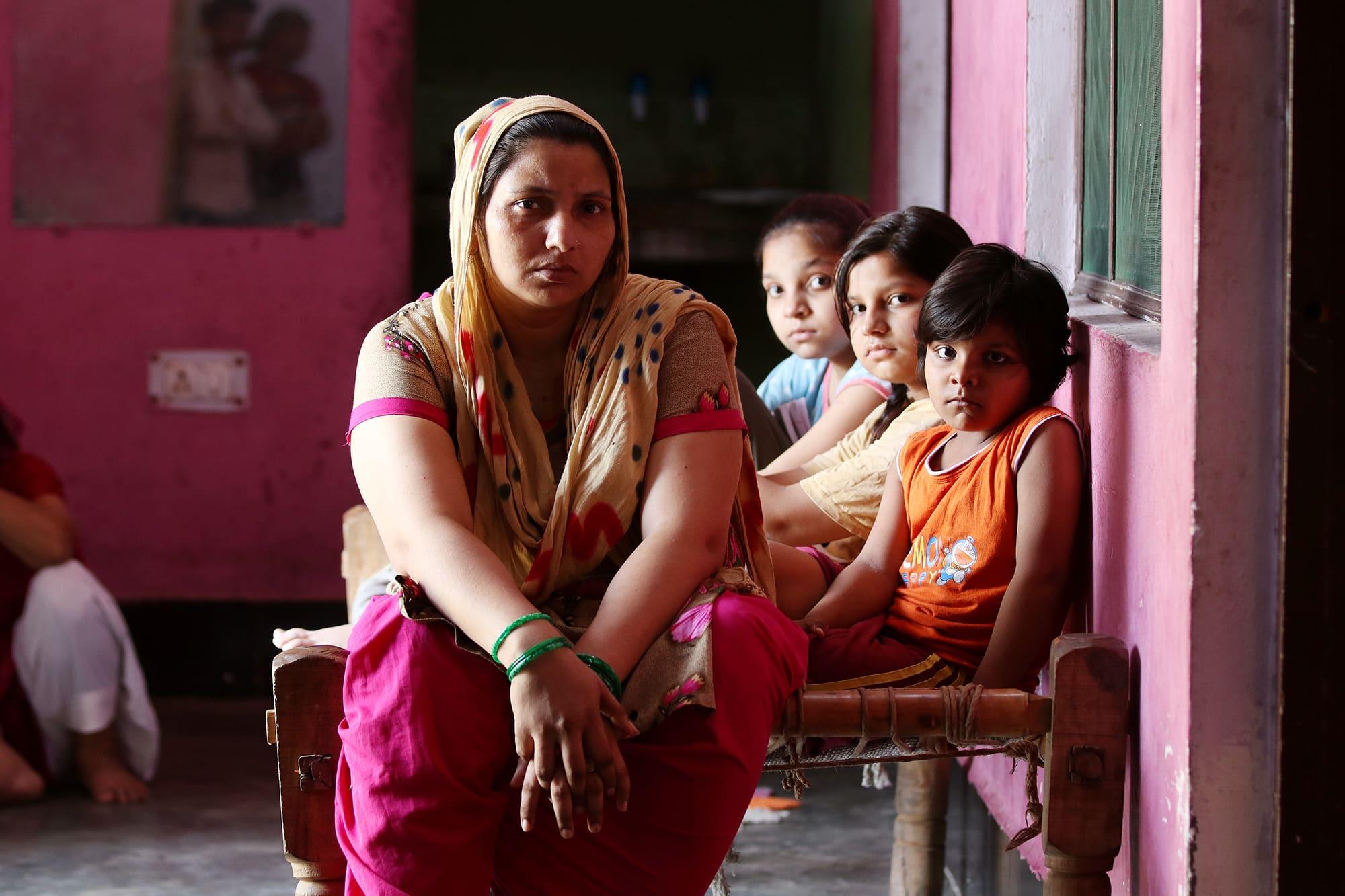 Kavita Gautam istuu roosan värisessä huoneessa kolmen lapsensa kanssa.