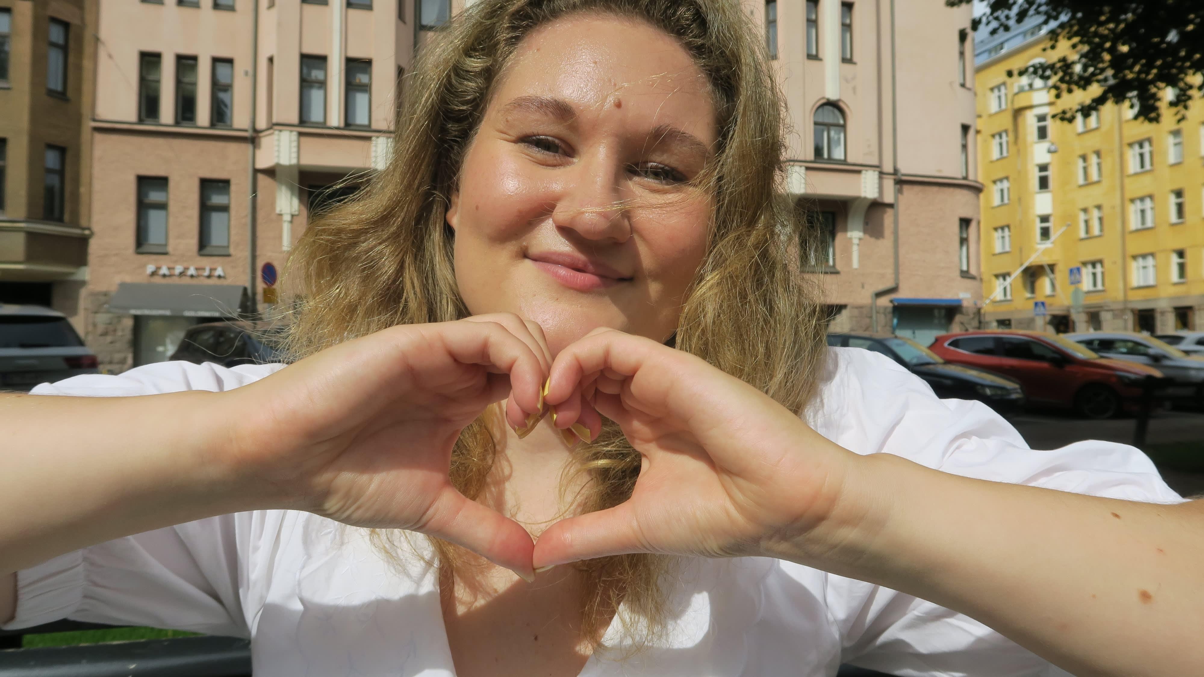 Vivi Mikkonen tekee käsillään sydämen kameraa kohti.
