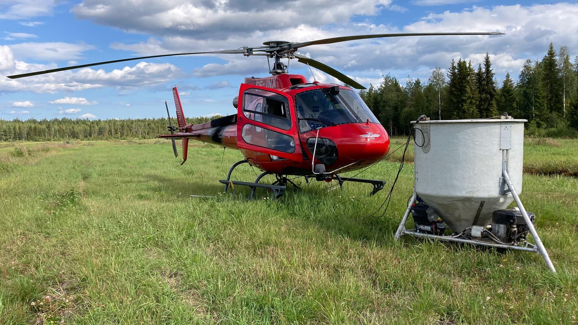Punainen helikopteri pellolla, edessä valkoinen lannoitussäiliö.
