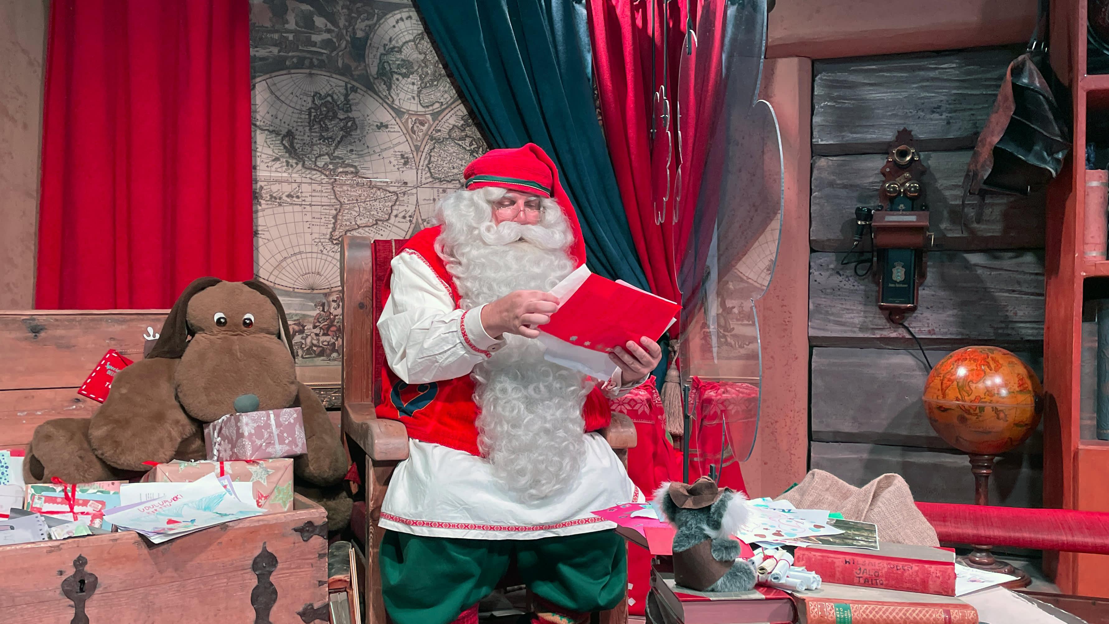 Joulupukki lukee kirjettä toimistossaan Napapiirin pajakylässä.