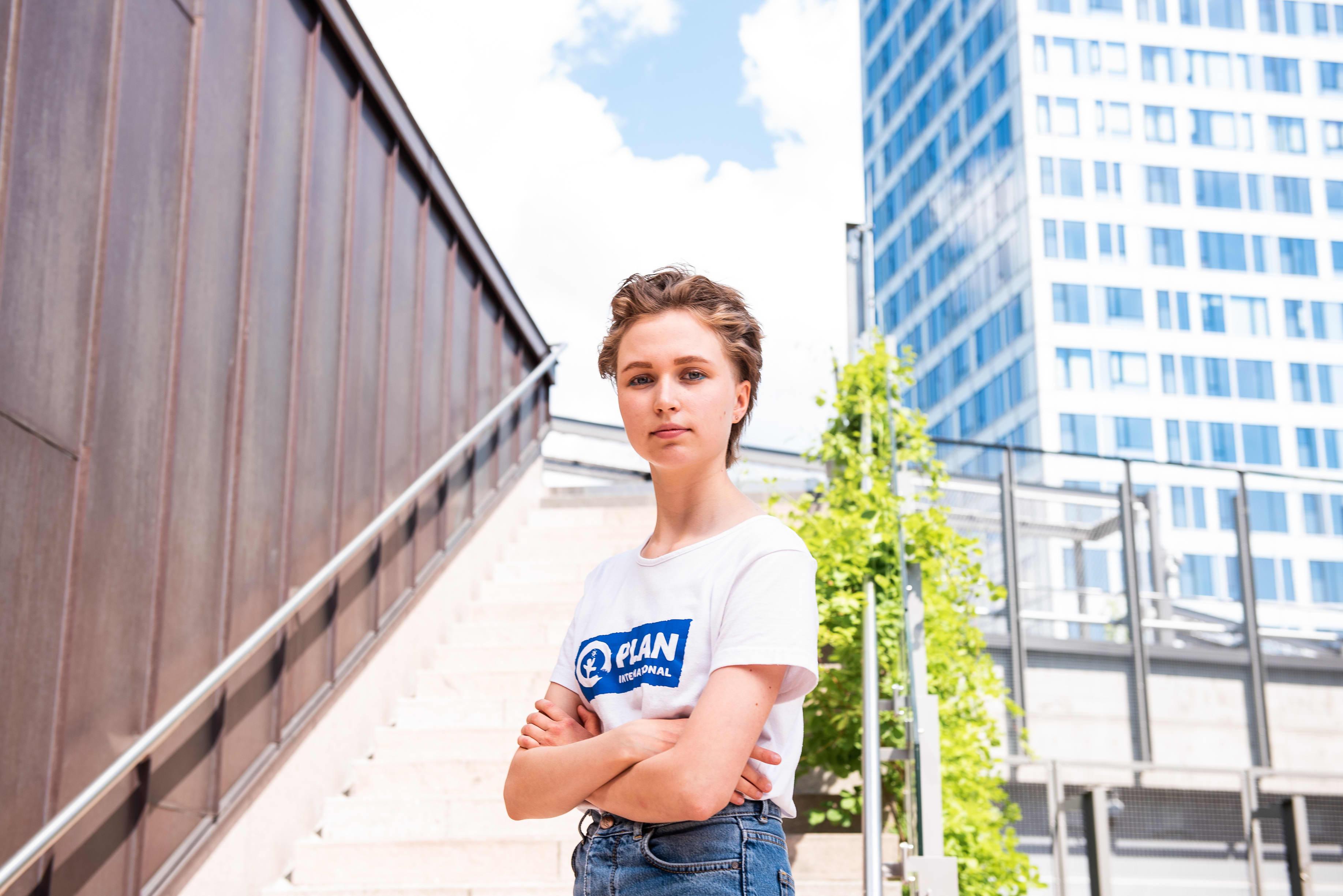 nuori nainen seisoo kaupungilla rapuissa, taustalla korkea rakennus