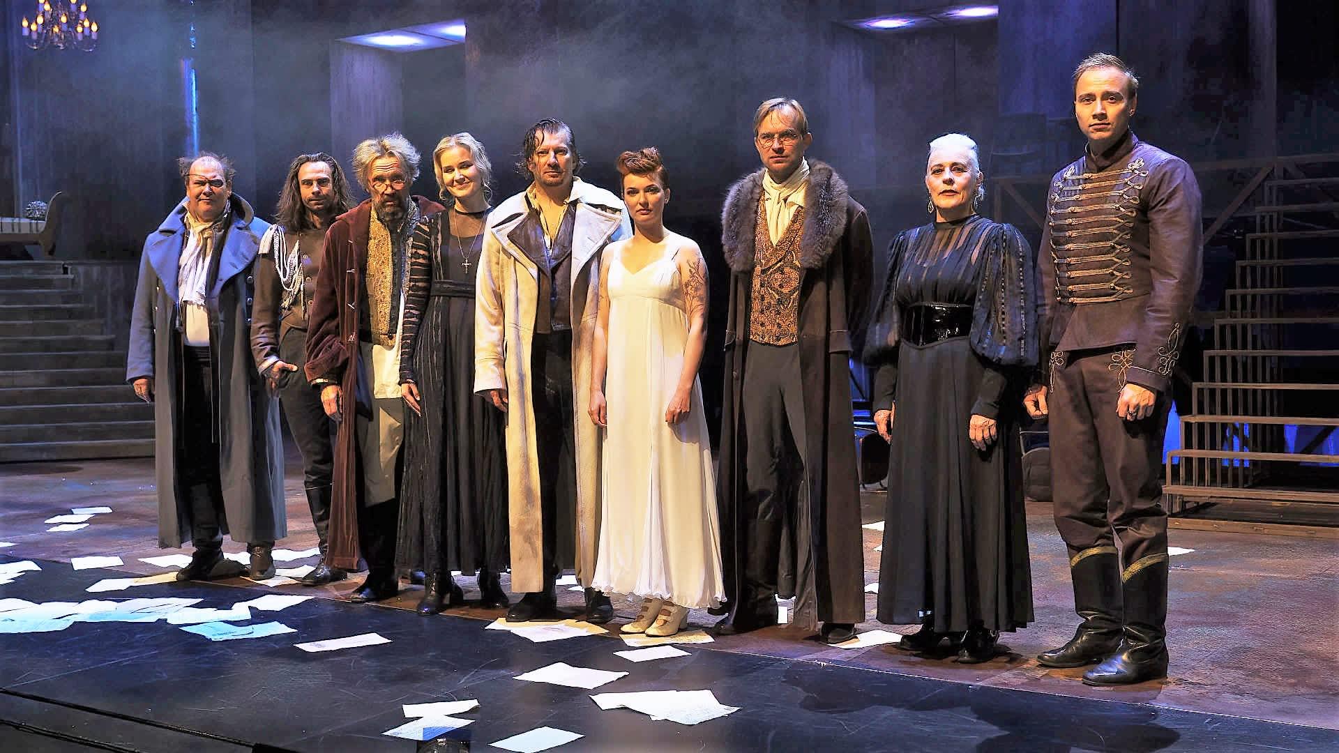 Lahden kaupunginteatterin Sota ja rauha -näytelmän esiintyjät rivissä näyttämön lavalla.