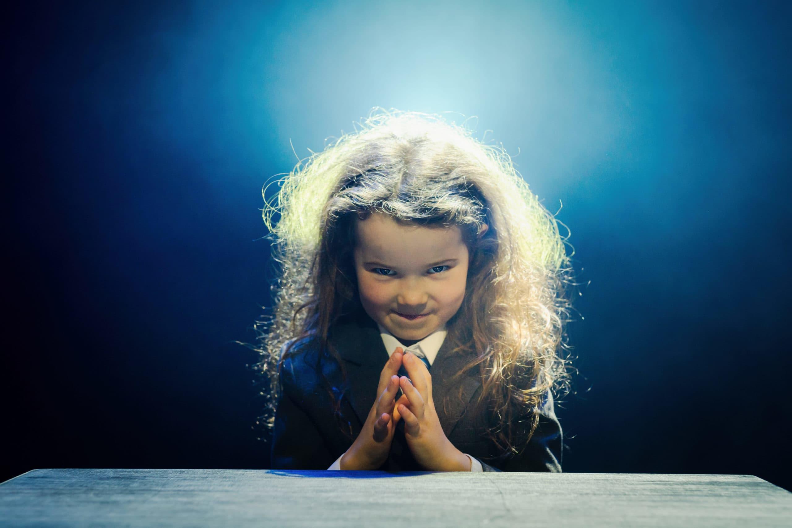 Pieni tyttö katsoo kameraan tukka pörrössä.