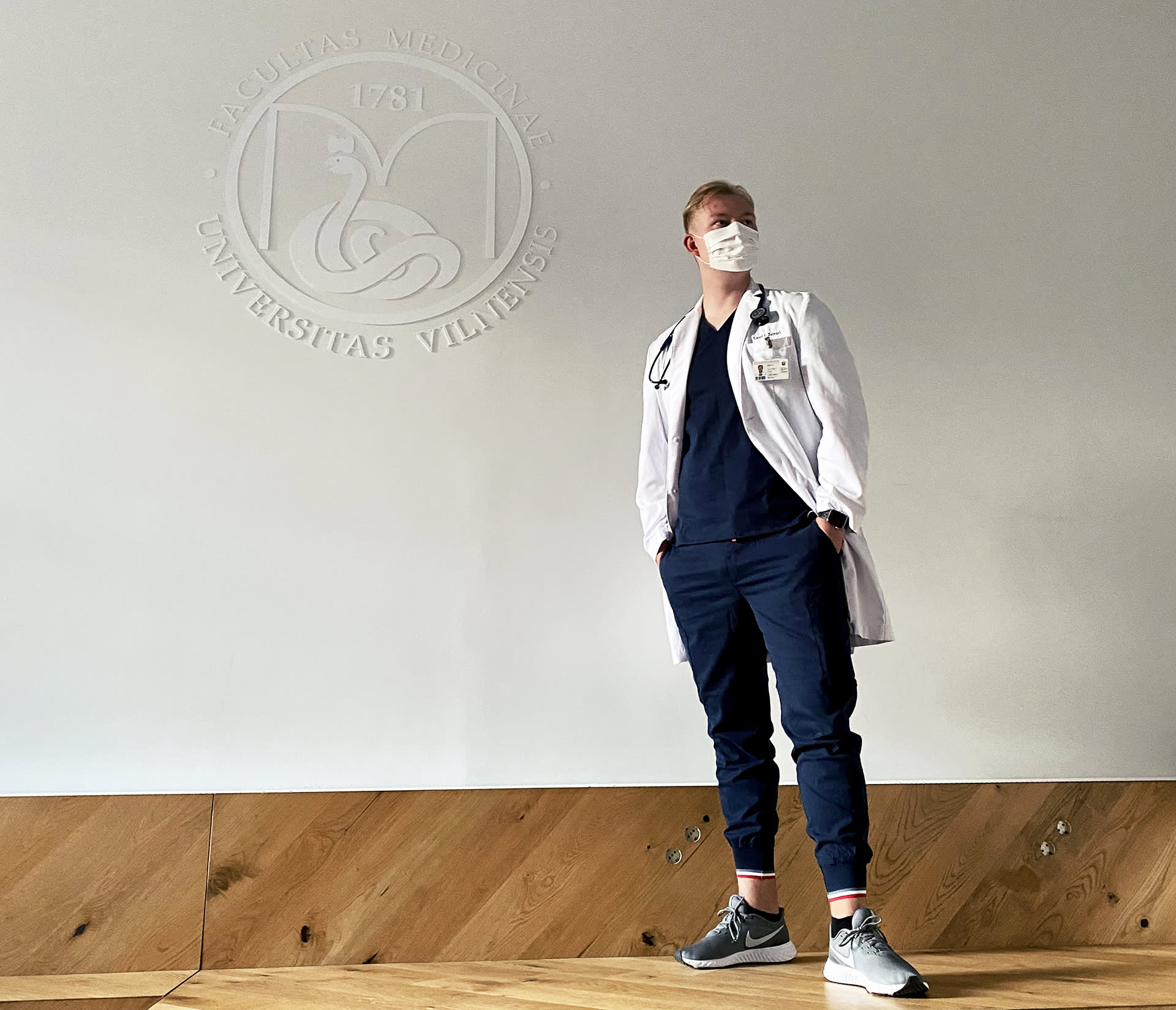 Nuori mies lääkärinvaatteissa seisoo Vilnan yliopiston logon alla.
