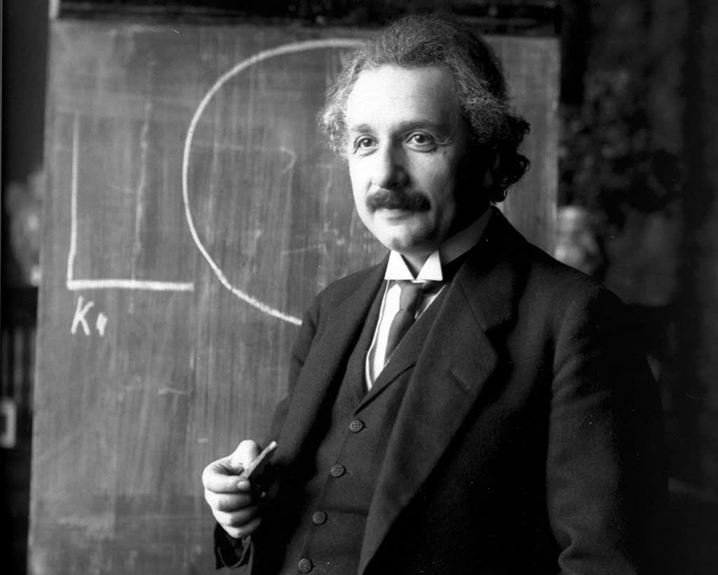 Liivipukuun pukeutunut Einstein liitutaulu  edessä.