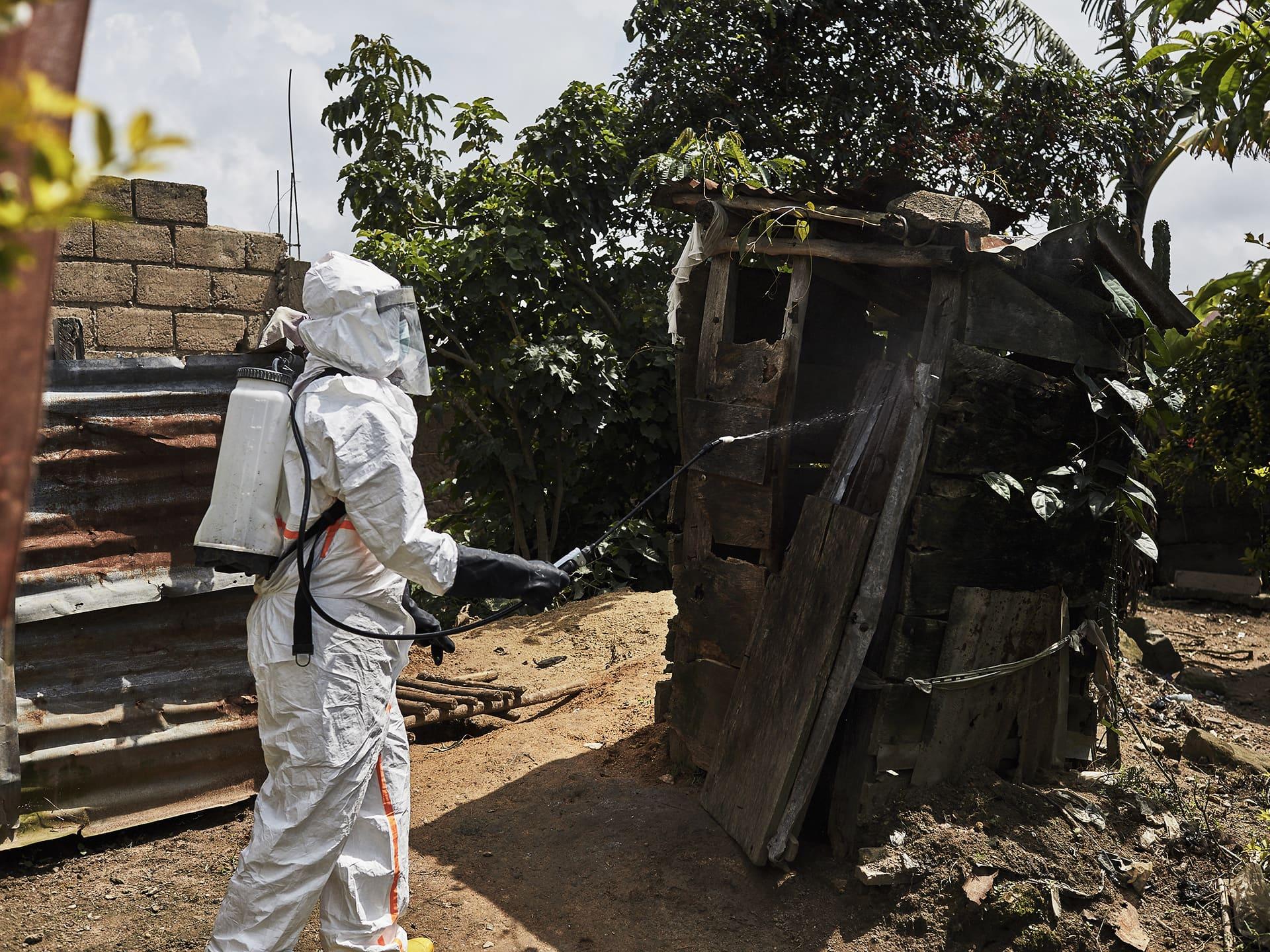 Suojavarusteisiin pukeutunut työntekijä ruiskuttaa desinfiointiainetta ebola-potilaan puutarhavajaan.