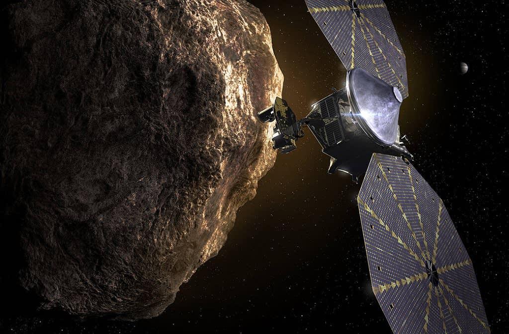 Luotain, jolla on kaksi isoa ja leveää aurinkopaneelisiipeä, ja  kuhmurainen asteroidi.