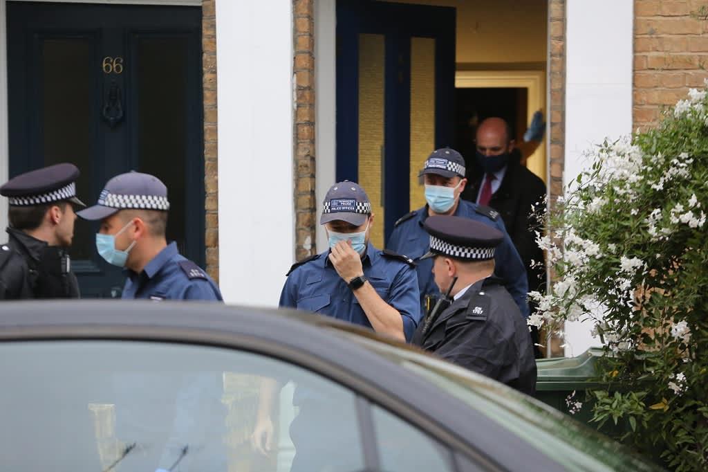 Poliiseja asunnon edustalla. Kuvassa etualalla näkyy auton kattoa.