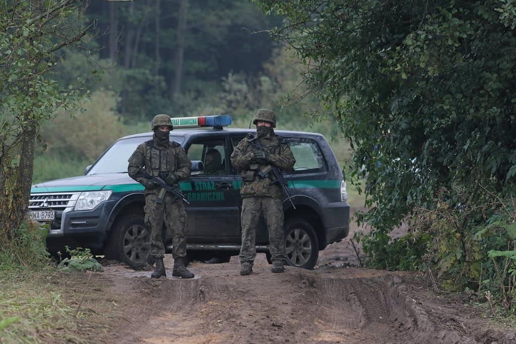 Kuvassa seisoo kaksi maastopukuista sotilasta. Heidän takanaan on maastoauto.