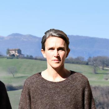 Kvinna med brun tröja i solsken. Gröna kullar och berg syns i bakgrunden