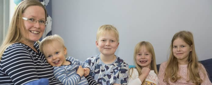 Viisihenkinen Heikkisten perhe kotisohvalla.