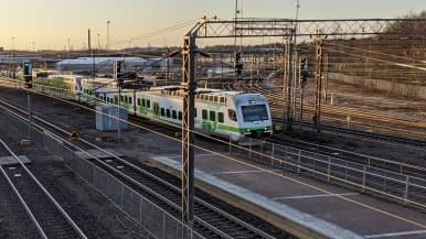 Lähijuna kulkee raiteilla Käpylän aseman liepeillä.