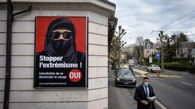 """Mies kävelee maski kasvoillaan """"burkakieltoa"""" kannattavan julisteen ohi."""