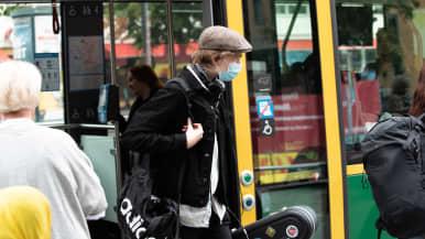 Mies kävelee raitiovaunusta ulos kasvomaski päässään.