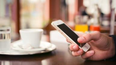 (Miehen) kädessä iPhone, taustalla kahvikuppi ja vesilasi.