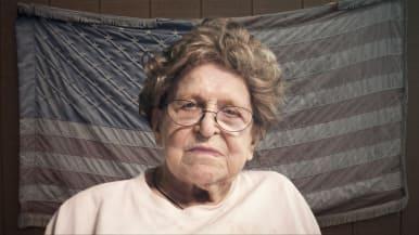 Iäkäs nainen Yhdysvaltain lipun edessä.