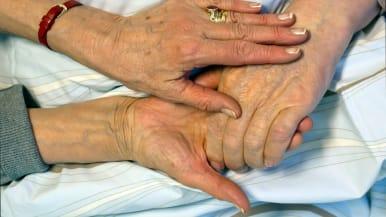Ikääntyvä nainen koskettaa puolisonsa kättä.