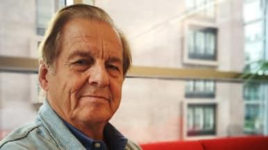 Tietokirjailija ja ulkomaankirjeenvaihtaja Rauli Virtanen istuu punaisella sohvalla.
