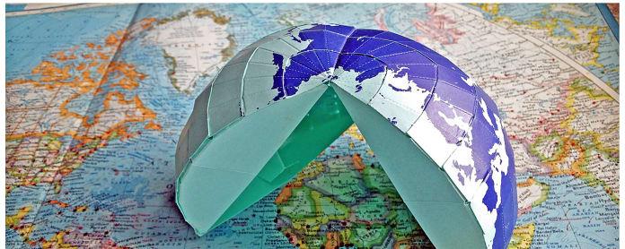 Japanilainen AuthaGraph-origamikartta puoliksi koottuna. Alla vanha karttakirja.