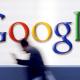 Mies kävelee vauhdilla Googlen logon ohi.