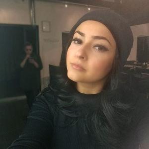 Angelina Davini-Pulkkinen som tittar in i kameran. Hon är klädd i svart tröja och svart mössa, och har långt svart hår.