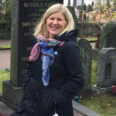 Kvinna står framför grav på Sandudds begravningsplats.