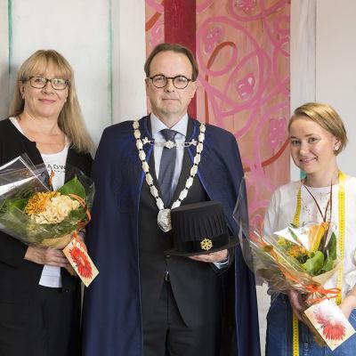 Lapin yliopiston rehtori Antti Syväjärvi päällään uusi rehtorin viitta, oikealla viitan tehnyt Riina Kaarlela ja vasemmalla hänen ohjaajansa professori Ana Nuutinen.