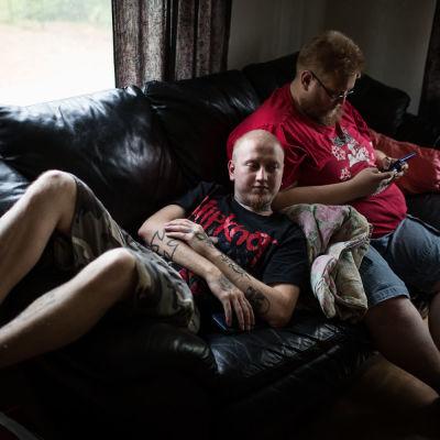 Sami och Saku Heinonen ligger i en soffa.