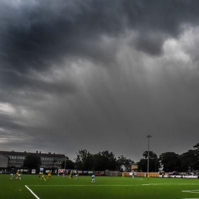 Mörka moln ovanför fotbollsplanen.