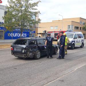 Poliser och brandmän står runt en bil som har krockat i centrum av en stad.