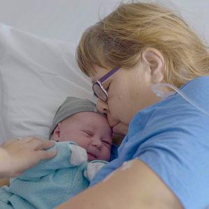 Nina suukottaa vastasyntynyttä tytärtään.