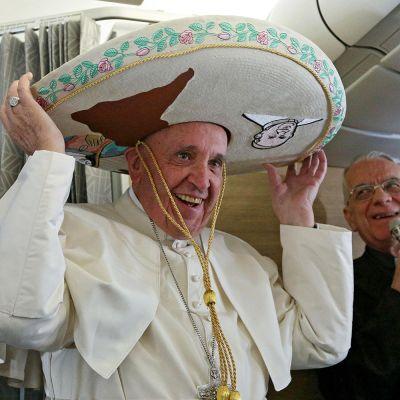Paavi Franciscus kokeili meksikolaiselta toimittajalta saamaansa sombreroa lentokoneessa matkalla Kuubaan perjantaina 12. helmikuuta.