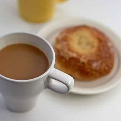 A mug of coffee and a bun.