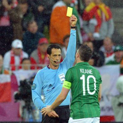 Tuomari Pedro Proenca nostaa keltaisen kortin Irlannin Robbie Keanelle.