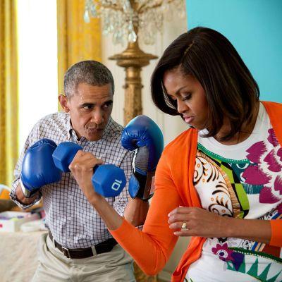 Presidentti Barack Obama hassuttelee nyrkkelyhanskat kädessä vaimonsa Michellen kanssa, joka pitää toisessa kädessään käsipainoa.
