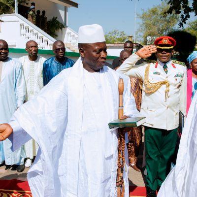 Valkoasuiset Jammeh ja Buhari seisovat ulkona punaisella matolla. Taustalla muita ihmisiä.
