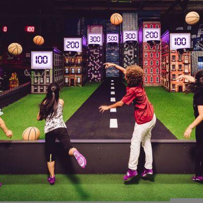 Lapset heittävät palloja maalitauluihin.
