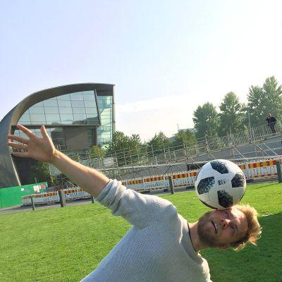 Kuvassa mies temppuilee jalkapallon kanssa.