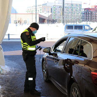 Rajavartiolaitoksen työntekijä tarkistaa matkustajan asiakirjoja.