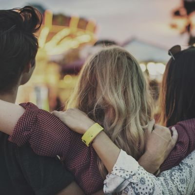 tre människor håller om varandra bakom ryggen
